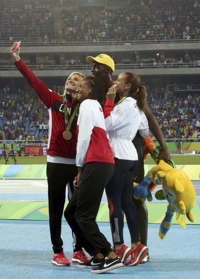 2016 Rio Olympics - Athletics - Victory Ceremony - Women's Heptathlon Victory Ceremony - Olympic Stadium - Rio de Janeiro, Brazil - 14/08/2016. Brianne Theisen-Eaton (CAN) of Canada, Nafissatou Thiam (BEL) of Belgium and Jessica Ennis-Hill (GBR) of Britain take a picture with Usain Bolt (JAM) of Jamaica, gold medallist in the men's 100m final. REUTERS/Alessandro Bianchi FOR EDITORIAL USE ONLY. NOT FOR SALE FOR MARKETING OR ADVERTISING CAMPAIGNS.