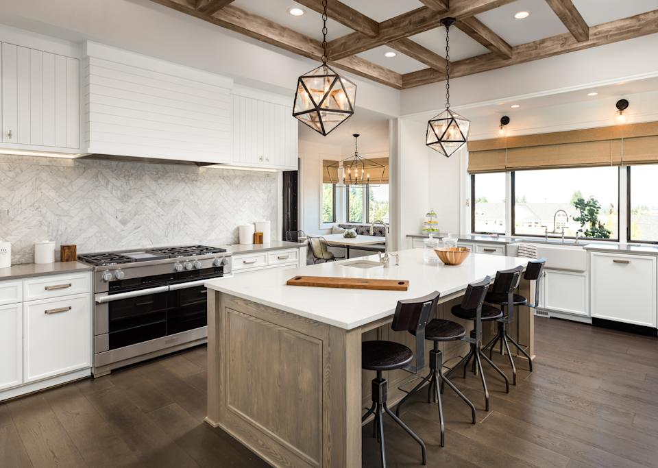 Kitchen Interior with Island, Sink, Cabinets, and Hardwood Floors in New Luxury Home. Includes elegant pendant light fixtures and wood beam ceiling