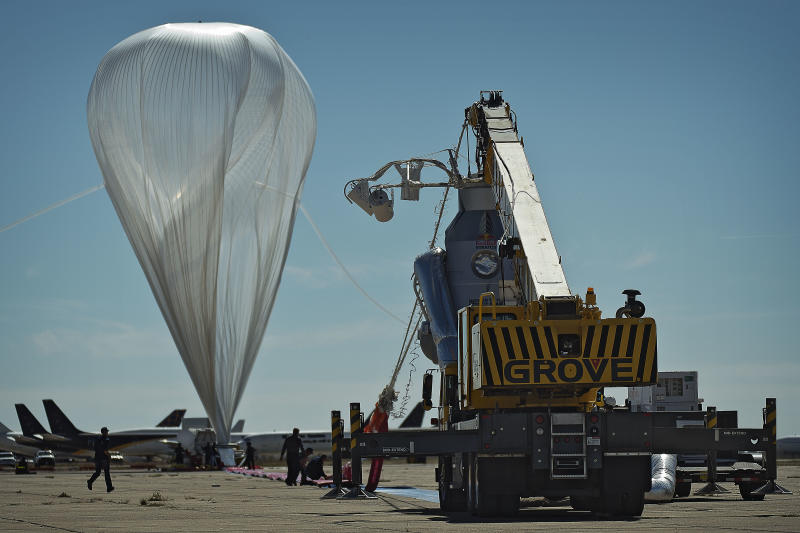 In this photo provided by Red Bull Stratos, the  55-story, ultra-thin helium balloon that was to carry extreme athlete Felix Baumgartner to his 23-mile free fall twists in the wind Tuesday, Oct. 9, 2012 in Roswell, N.M.  A 25 mph gust of wind rushed so fast that it spun the still-inflating balloon as if it was a giant plastic grocery bag, raising concerns at mission control about whether it was damaged from the jostling. The jump will be postponed until at least Thursday. (AP Photo/Red Bull Stratos, Joerg Mitter)