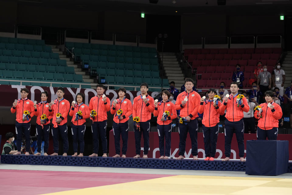 Members of Japan's team pose with their silver medals during the medal ceremony in team judo competition at the 2020 Summer Olympics, Saturday, July 31, 2021, in Tokyo, Japan. (AP Photo/Vincent Thian)
