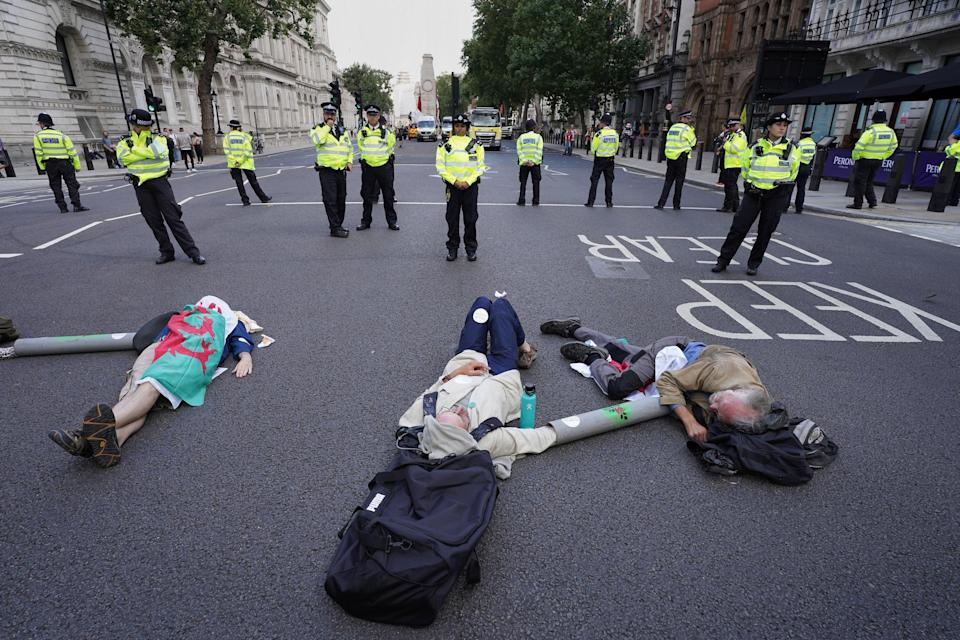 Demonstrators from Extinction Rebellion lay on the floor in Whitehall, London (PA)