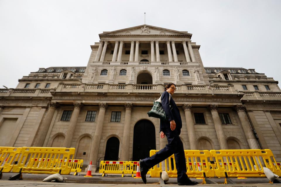 A pedestrian walks past the Bank of England in London on June 17, 2020. - The Bank of England, confronted by Britain's collapsing coronavirus-ravaged economy, will on June 18 reveal the outcome of its latest monetary policy meeting with analysts predicting more stimulus. The British central bank has been at the forefront of economic fire-fighting over this year's deadly COVID-19 emergency -- and could expand its quantitative easing (QE) stimulus in an attempt to kickstart growth. (Photo by Tolga Akmen / AFP) (Photo by TOLGA AKMEN/AFP via Getty Images)
