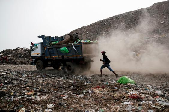 A waste collector runs behind a truck carrying rubbish