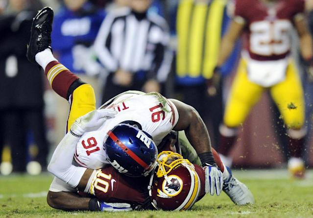 Washington Redskins quarterback Robert Griffin III (10) is sacked by New York Giants defensive end Justin Tuck (91) during the second half of an NFL football game Sunday, Dec. 1, 2013, in Landover, Md. The Giants won 24-17. (AP Photo/Nick Wass)