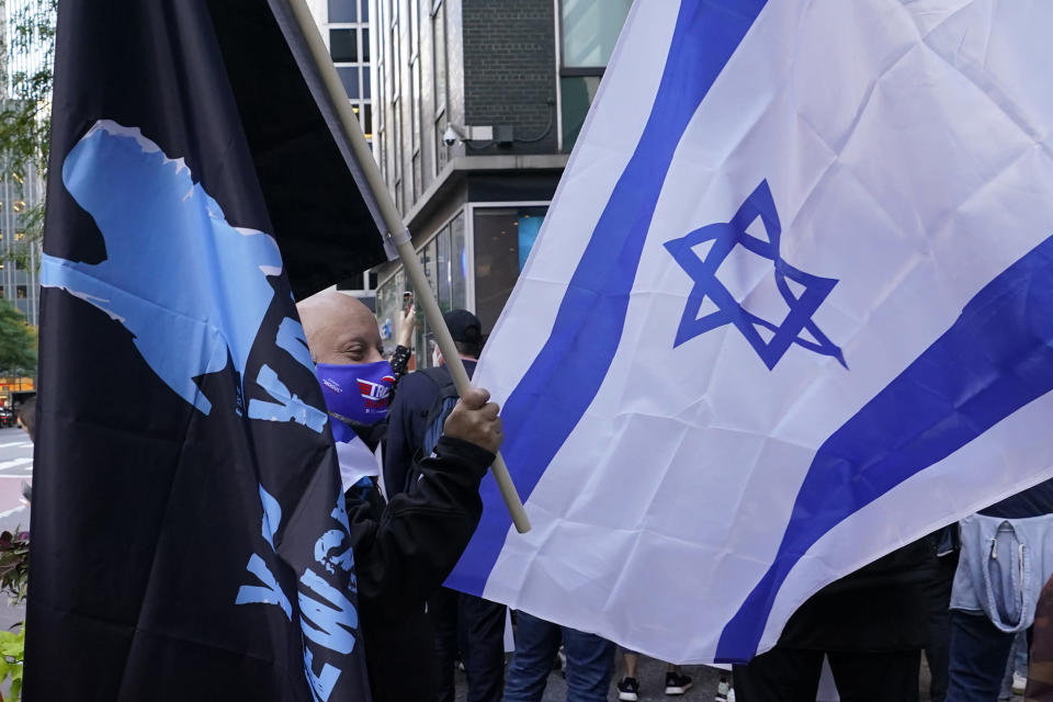 A protester holds a flag as he stands beside another bearing an Israeli flag while joining a group of protesters outside the offices of New York Gov. Andrew Cuomo, Thursday, Oct. 15, 2020, in New York. Three Rockland County Jewish congregations have filed a lawsuit accusing Gov. Andrew Cuomo of engaging in a streak of anti-Semitic discrimination with a crackdown on religious gatherings. The Manhattan federal court lawsuit filed Wednesday says Cuomo has made numerous discriminatory statements about the Jewish Orthodox community. (AP Photo/Kathy Willens)