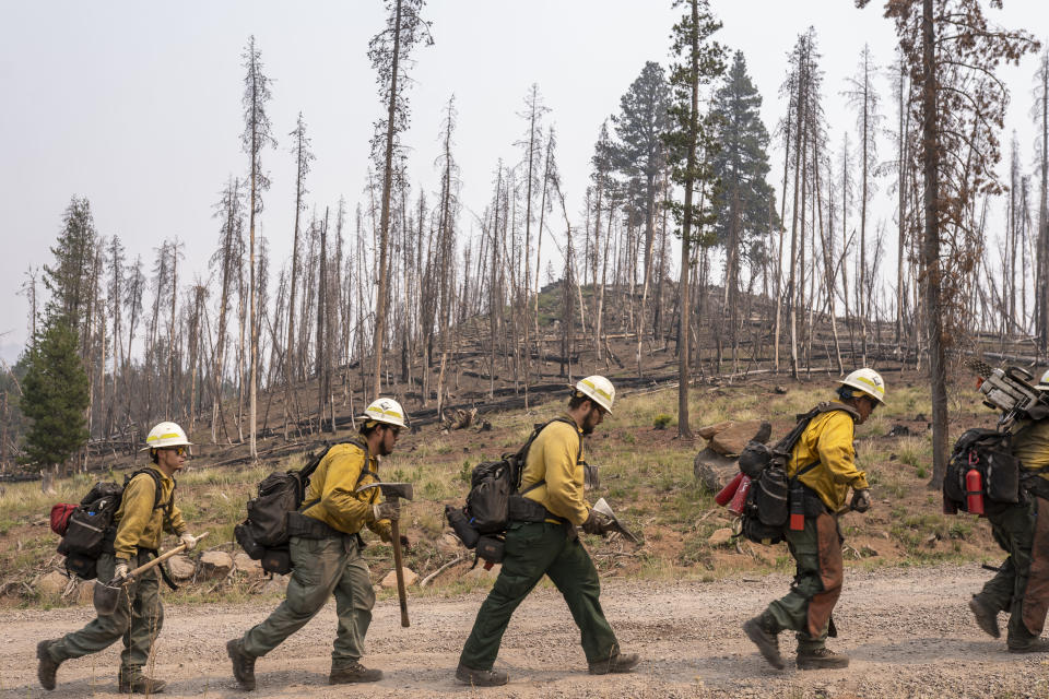 Firefighters from New Mexico walk toward the Northwest edge of the Bootleg Fire while working to build a containment line on Friday, July 23, 2021, near Paisley, Ore. (AP Photo/Nathan Howard)