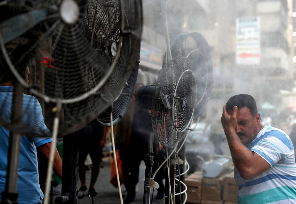 A man stands by fans spraying water vapour deployed by donors to cool down pedestrians in Iraq's capital Baghdad  (AFP via Getty Images)