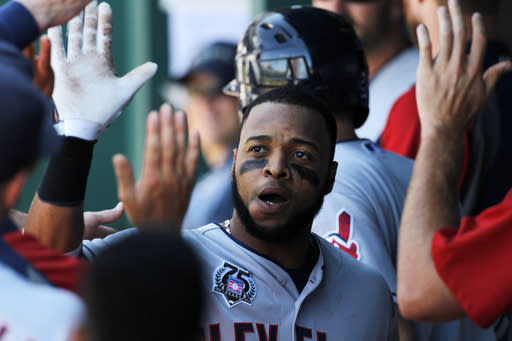 Cleveland Indians' Carlos Santana is congratulated in the dugout after hitting a two-run home run in the ninth inning of a baseball game against the Kansas City Royals at Kauffman Stadium in Kansas City, Mo., Sunday, July 27, 2014. The Indians won 10-3. (AP Photo/Colin E. Braley)