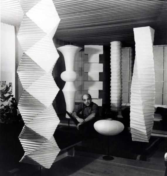 This photo provided by The Isamu Noguchi Foundation and Garden Museum shows Noguchi, the late modernist sculptor, in his studio in Long Island City, N.Y., in the 1960s, surrounded by his lighting sculptures. Japanese paper lanterns used in ancestor worship customs were the inspiration for Noguchi's lamp designs, which he called akari, the Japanese word for light. The lamps became classics of mid-20th century modern home design, and while the concept has been widely imitated, Noguchi's original designs are still produced and sold by his foundation. (AP Photo/The Isamu Noguchi Foundation and Garden Museum)