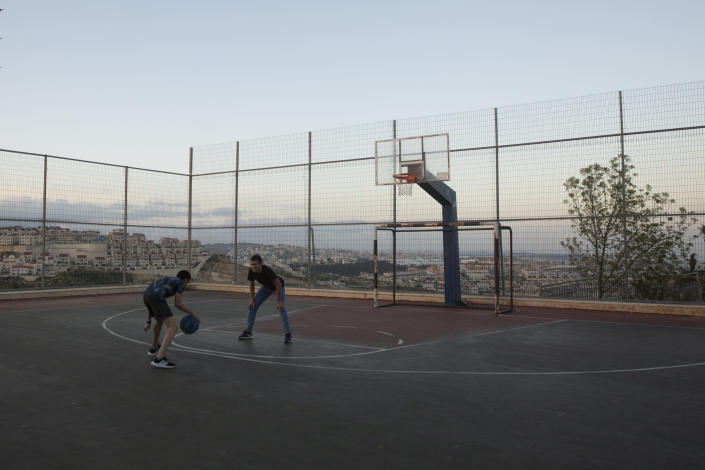 Teens play basketball in the West Bank Jewish settlement of Efrat, Tuesday, March 16, 2021. Israel went on an aggressive settlement spree during the Trump era, according to an AP investigation, pushing deeper into the occupied West Bank than ever before and putting the Biden administration into a bind as it seeks to revive Mideast peace efforts. (AP Photo/Maya Alleruzzo)