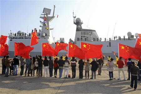 Chinese nationals living in Cyprus wave Chinese national flags as the Chinese frigate Yancheng comes in to dock at Limassol port