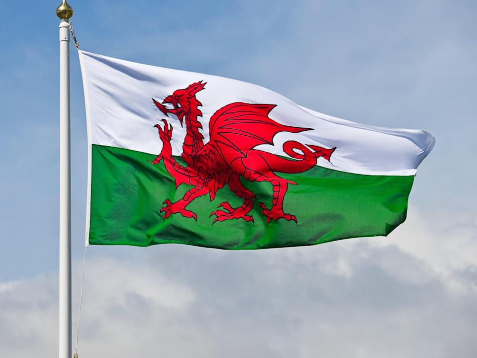 The welsh flag, a red dragon on a green and white background, flutters in the wind against a blue sky. (Getty Images/iStockphoto)