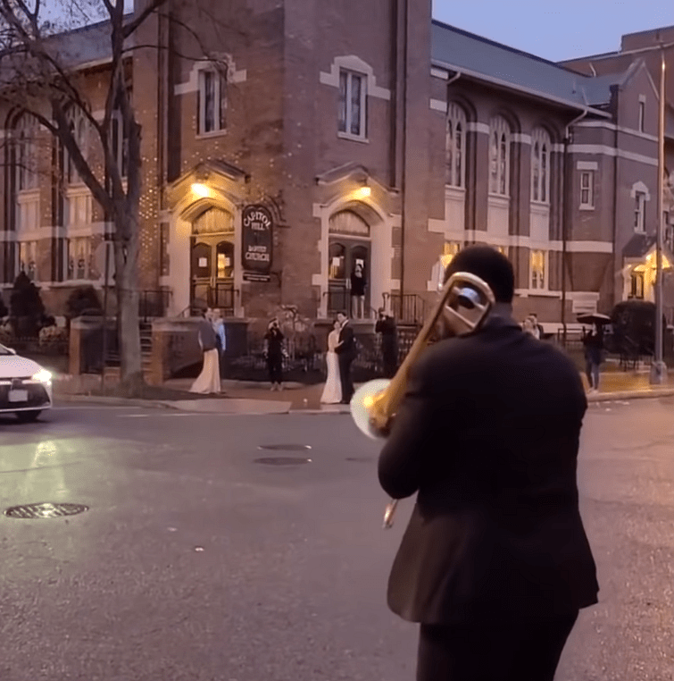 A musician plays a song for the newlywed couple dancing on the street