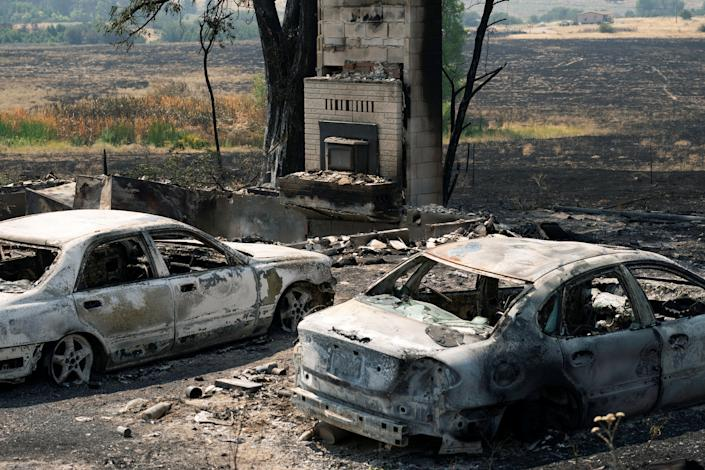 Burned cars sit outside a home destroyed by the Chuweah Creek Fire as wildfires devastate Nespelem in eastern Washington state.