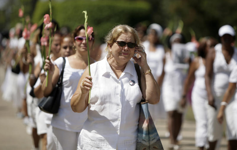 Laura Pollan, leader of the Cuban dissident group Ladies in White, uses a cell phone as she the participate in the group's weekly march in in Havana, Cuba, Sunday, March. 27, 2011. The Ladies in White is a group of relatives of Cuban dissidents who were imprisoned. (AP Photo/Javier Galeano)