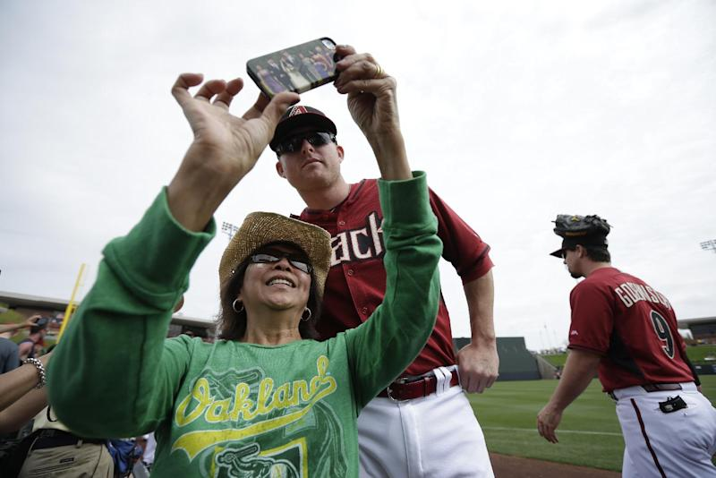 Lee Uehima, left, takes a picture with Arizona Diamondbacks left fielder Mark Trumbo, center, as Diamondbacks catcher Tuffy Gosewisch, right, walks past, before playing the Oakland Athletics in an exhibition baseball game Thursday, March 6, 2014, in Scottsdale, Ariz. (AP Photo/Gregory Bull)