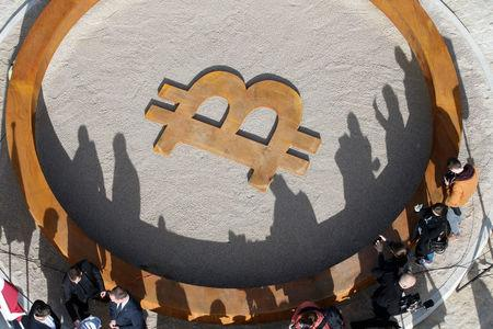 People attend the opening ceremony of world's first public Bitcoin monument, placed at a roundabout connecting two roads at the city centre in Kranj, Slovenia, March 13, 2018. REUTERS/Borut Zivulovic