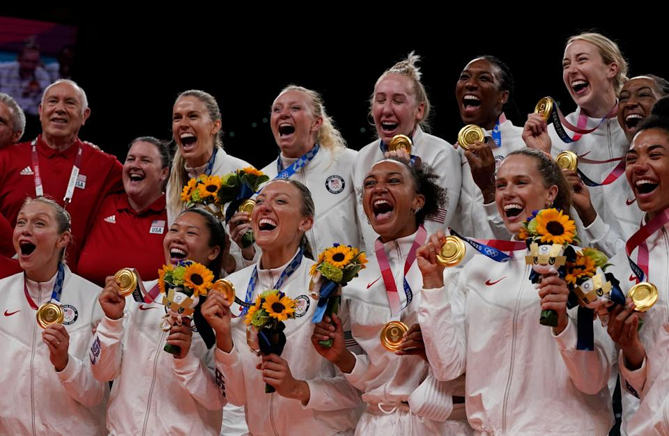 The U.S. women's volleyball team celebrates with their gold medals.