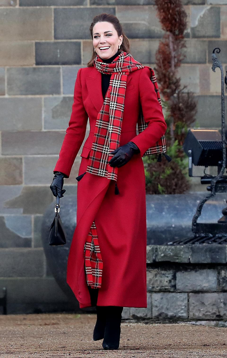 Catherine, Duchess of Cambridge wears a red coat and red plaid scarf on a visit to Cardiff Castle on December 08, 2020 in Cardiff, Wales.