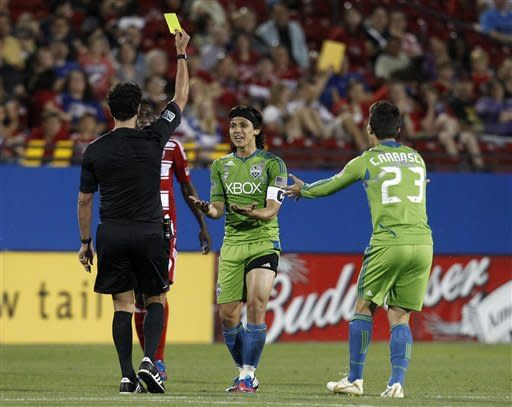 Referee Fotis Bazakos, left, issues a yellow card to Seattle Sounders' Fredy Montero, center, as Montero and Servando Carrasco (23) plead with Bazakos in the second half of an MLS soccer game against FC Dallas, Wednesday, May 9, 2012, in Frisco, Texas. Montero scored both goals in the Sounders' 2-0 win. (AP Photo/Tony Gutierrez