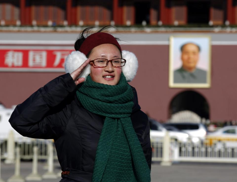 A woman salutes as she poses for her souvenir picture in front of a large portrait of the late Chairman Mao Zedong at Tiananmen Square in Beijing December 26, 2013. China celebrated the 120th birthday of Mao, the founder of modern China, on Thursday, but with scaled-back festivities as President Xi Jinping embarks on broad economic reforms which have unsettled leftists. REUTERS/Kim Kyung-Hoon (CHINA - Tags: ANNIVERSARY POLITICS)