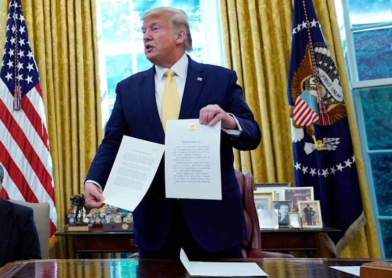 U.S. President Donald Trump holds a letter from China's President Xi Jinping during a meeting with China's Vice Premier Liu He in the Oval Office at the White House after two days of trade negotiations in Washington, U.S., October 11, 2019. REUTERS/Yuri Gripas