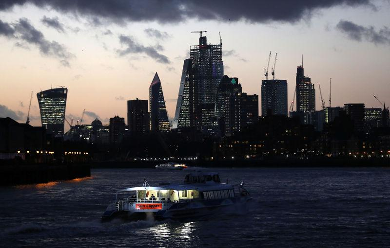 A river boat cruises down the River Thames as the sun sets behind the Canary Wharf financial district of London