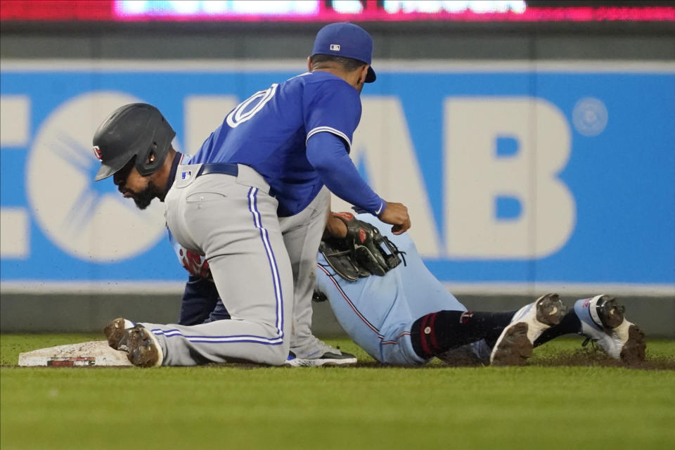 Minnesota Twins' Byron Buxton, left, steals second base, beating the tag attempt by Toronto Blue Jays second baseman Marcus Semien in the fifth inning of a baseball game, Saturday, Sept. 25, 2021, in Minneapolis. (AP Photo/Jim Mone)