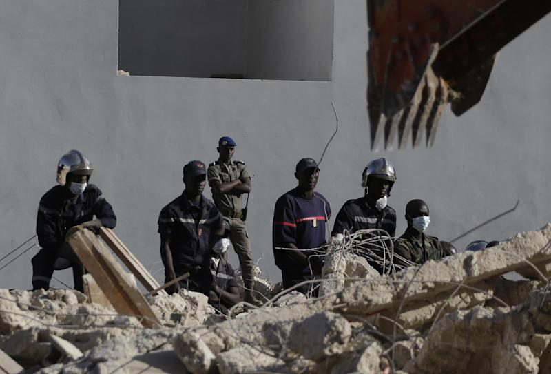 Police look for signs of life from people buried as a digger clears rubble from the site of a four-storey building that collapsed during construction, in a neighborhood full of buildings under construction, in Dakar, Senegal, Friday, March 8, 2013. Omar Samb Gueye, the local chief of the Ouakam area where the building was being constructed, said two people were killed and two injured when the building folded in on itself and collapsed in Senegal's capital, Dakar. He said the building was being constructed twice as tall as the two-storey height for which it had been authorized. (AP Photo/Rebecca Blackwell)