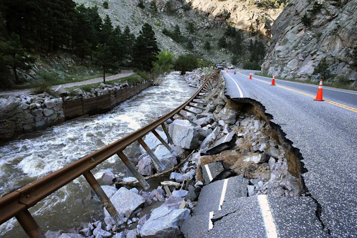 A guardrail hangs away from a closed canyon road, which links Boulder with the mountain town of Nederland, and which is washed out in places by recent flooding, up Boulder Canyon, west of Boulder, Colo., Friday Sept. 20, 2013. With snow already dusting Colorado's highest peaks, the state is scrambling to replace key mountain highways washed away by flooding. More than 200 miles of state highways and at least 50 bridges were damaged or destroyed, not counting many more county roads. (AP Photo/Brennan Linsley)