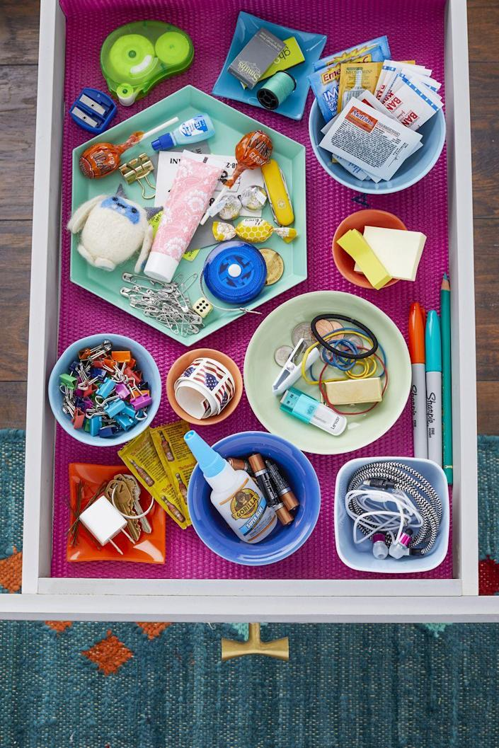 """<p>Once you empty out your drawer, suck out dust and crumbs with your vacuum's nozzle. """"Toss or relocate any items you no longer need or that don't belong there,"""" Forte says. Everything else goes back, but this time in an organized manner. Repurpose pretty plates and bowls to store cords, stamps, and other odds and ends. A nonslip liner will help keep everything in place. </p>"""