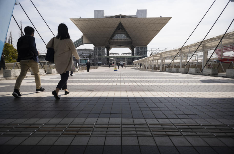 People walk towards the Tokyo International Exhibition Center, also known as Tokyo Big Sight, in Tokyo Thursday, April 8, 2021. The exhibition center is a planned venue for the Tokyo 2020 Olympic and Paralympic Games, rescheduled to start in July 2021. Many preparations are still up in the air as organizers try to figure out how to hold the postponed games in the middle of a pandemic. (AP Photo/Hiro Komae)
