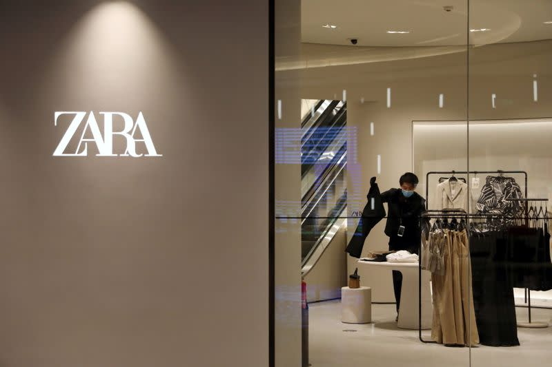FILE PHOTO: A staff member sorts clothes inside a clothing store at a newly opened shopping mall in Beijing, China