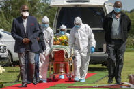 FILE - In this April 16, 2020, file photo, pallbearers wearing personal protective equipment suits lift the casket containing the remains of Benedict Somi Vilakasi for his burial ceremony at the Nasrec Memorial Park outside Johannesburg, South Africa. Africa's confirmed coronavirus cases have surpassed 1 million, but global health experts tell The Associated Press the true toll is several times higher. (AP Photo/Jerome Delay, File)