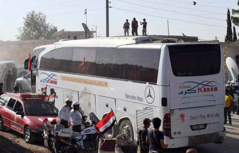 This photo released by the Syrian official news agency SANA, shows Syrians being evacuated in buses from the two pro-government villages of Foua and Kfarya, at Tel el-Eis, the crossing between Aleppo and Idlib provinces, Syria, Thursday, July 19, 2018. Over 7,000 people from the villages in the country's northwest that were besieged by the rebels for three years have been evacuated, Syria's state-run media reported Thursday. (SANA via AP)
