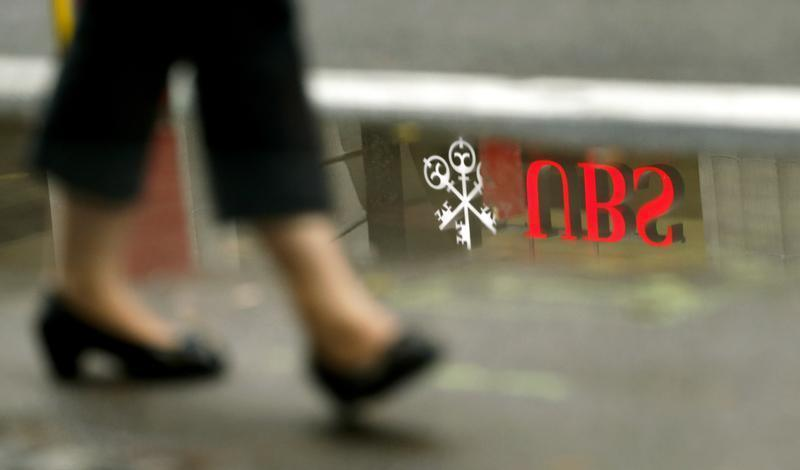 The logo of Swiss bank UBS is reflected in a puddle in Zurich