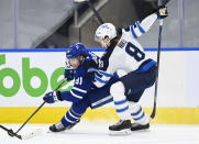 Toronto Maple Leafs center John Tavares (91) tries to drive past Winnipeg Jets defenseman Sami Niku (8) during the third period of an NHL hockey game in Toronto on Monday, Jan. 18, 2021. (Nathan Denette/The Canadian Press via AP)