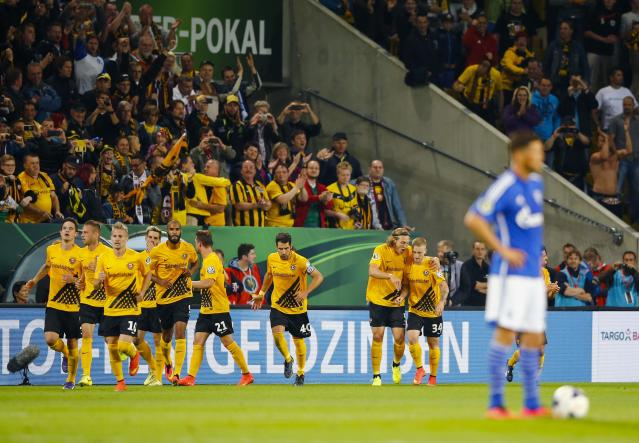 Dynamo Dresden players (L) celebrate after they scored against Schalke 04 during their German soccer cup (DFB Pokal) match in Dresden August 18, 2014. REUTERS/Thomas Peter (GERMANY - Tags: SPORT SOCCER TPX IMAGES OF THE DAY) DFB RULES PROHIBIT USE IN MMS SERVICES VIA HANDHELD DEVICES UNTIL TWO HOURS AFTER A MATCH AND ANY USAGE ON INTERNET OR ONLINE MEDIA SIMULATING VIDEO FOOTAGE DURING THE MATCH