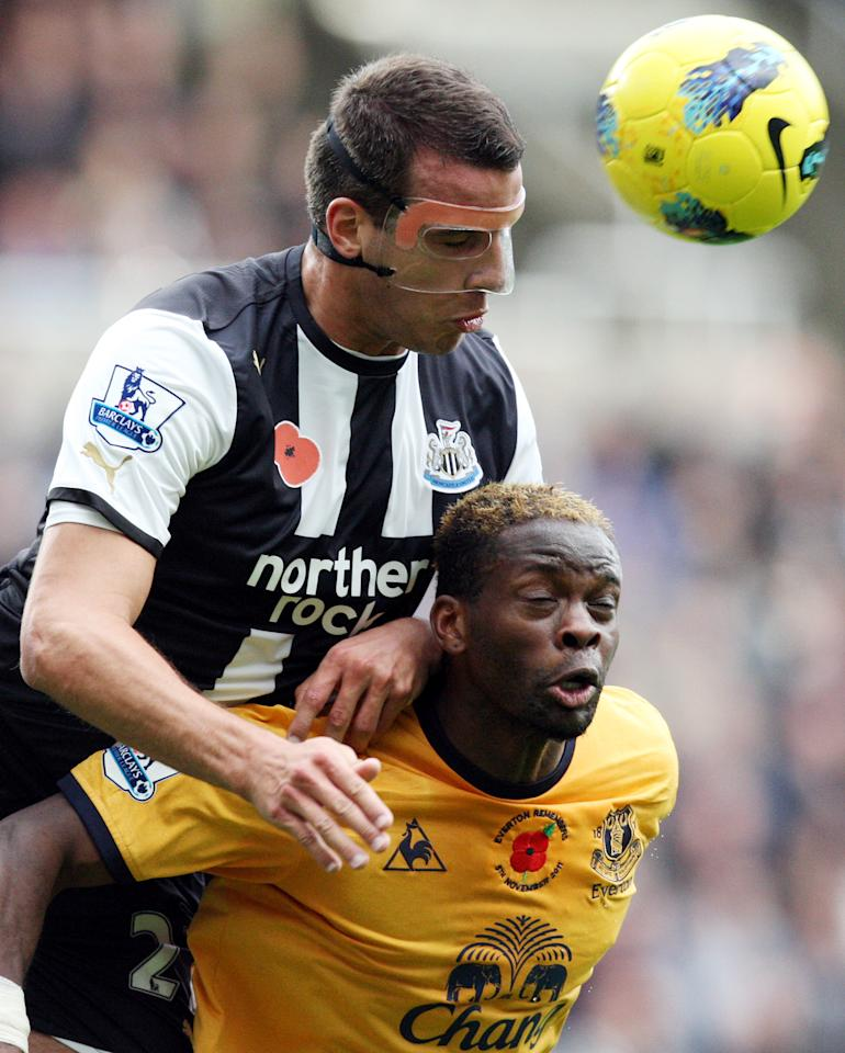 Newcastle United's Steven Taylor, top, vies for the ball with Everton's Louis Saha, bottom, during their English Premier League soccer match at St James' Park, Newcastle, England, Saturday, Nov. 5, 2011. (AP Photo/Scott Heppell)