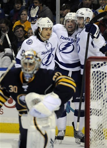 Buffalo Sabres' Ryan Miller (30) reacts as Tampa Bay Lightning' Steve Downie, left, Steven Stamkos, center, and Teddy Purcell celebrate a second-period goal by Steven Stamkos during an NHL hockey game in Buffalo, N.Y., Saturday, Feb. 11, 2012. (AP Photo/Gary Wiepert)