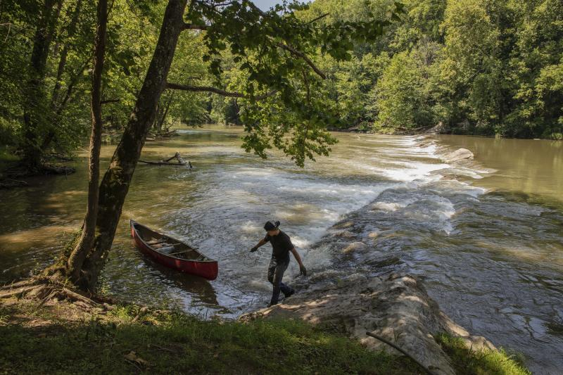 This July 26, 2019 photo provided by the Nature conservancy shows a StreamSweepers employee pulls a canoe to shore on the Clinch River, Va. The Cumberland Forest Project protects 253,000 acres of Appalachian forest in Tennessee, Kentucky, and Virginia and is one of TNC's largest-ever conservation efforts in the eastern United States. StreamSweepers is a not for profit river maintenance and restoration service, staffed by young adults from Central Virginia. StreamSweepers assess the ecological health of rivers in the Piedmont portion of the state and remove small to large trash items from the river bed and banks. (Travis Dove/The Nature Conservancy via AP)
