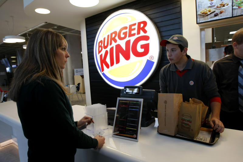 A customer purchases a meal at a Burger King restaurant in Marseille-Provence airport, in Marignane, France, Saturday, Dec. 22, 2012. Fifteen years after leaving France, the U.S. hamburger chain Burger King returned with the opening of a restaurant in Marseille-Provence airport. (AP Photo/Claude Paris)