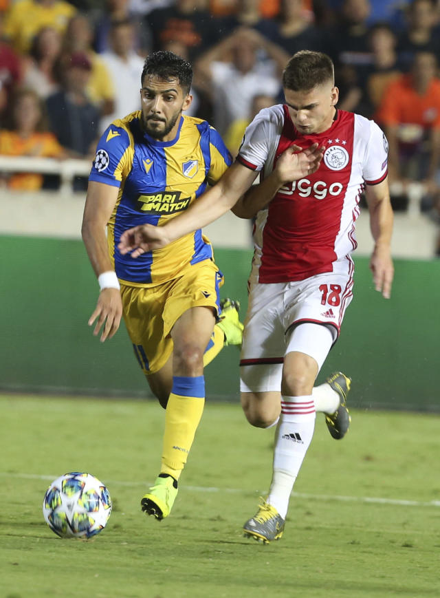 Ajax's Razvan Marin, right, challenges for the ball with APOEL's Musa Suleiman during the Champions League qualifying play-off first leg soccer match between APOEL Nicosia and AFC Ajax at GSP stadium in Nicosia, Cyprus, Tuesday, Aug. 20, 2019.(AP Photo/Philippos Christou)