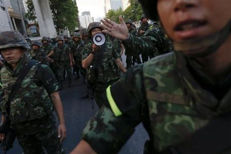 Soldiers try to control a crowd protesting against military rule in central Bangkok