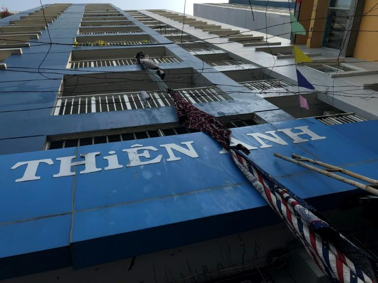 Improvised escape materials hang from a balcony at an apartment building after a fire broke out in Vietnam's southern commercial hub of Ho Chi Minh City early on March 23