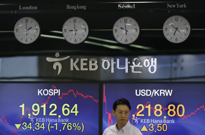 A currency trader walks by the screens showing the Korea Composite Stock Price Index (KOSPI), left, and the foreign exchange rate between U.S. dollar and South Korean won at the foreign exchange dealing room in Seoul, South Korea, Tuesday, Aug. 6, 2019. Asian stocks followed Wall Street lower on Tuesday after China let its currency sink and halted purchases of U.S. farm goods, fueling fears Beijing's trade war with President Donald Trump will harm the global economy. (AP Photo/Lee Jin-man)