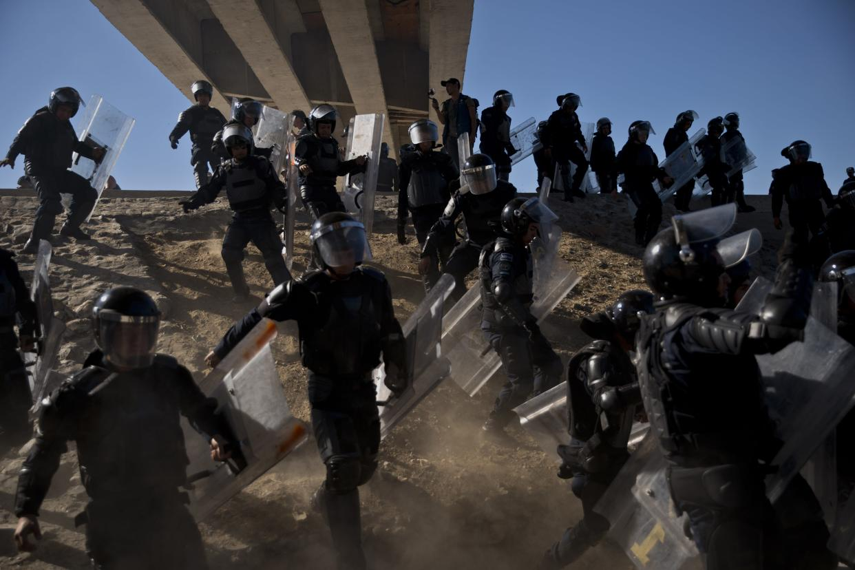 Mexican police run as they try to keep migrants from getting past the Chaparral border crossing in Tijuana, Mexico, on Sunday near San Ysidro, Calif. (Photo: Ramon Espinosa/AP)