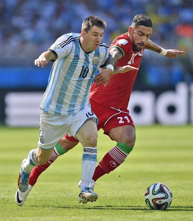 Argentina's Lionel Messi and Iran's Ashkan Dejagah push each other as they chase the ball during the group F World Cup soccer match between Argentina and Iran at the Mineirao Stadium in Belo Horizonte, Brazil, Saturday, June 21, 2014. (AP Photo/Martin Meissner)