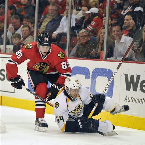 Chicago Blackhawks' Patrick Kane (88) and Nashville Predators' Victor Bartley (64) collide during the second period of an NHL hockey game Friday, April 19, 2013, in Chicago. (AP Photo/Jim Prisching)