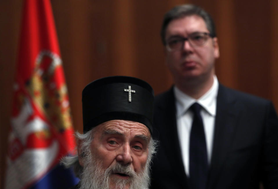 FILE - In this March 15, 2020, file photo, Serbian President Aleksandar Vucic, back, listens Serbian Patriarch Irinej during a statement in Belgrade, Serbia. Serbia's Orthodox Church said Friday, Nov. 20, 2020, the leader, Patriarch Irinej, has died after testing positive for the coronavirus. He was 90.(AP Photo/Darko Vojinovic, File)